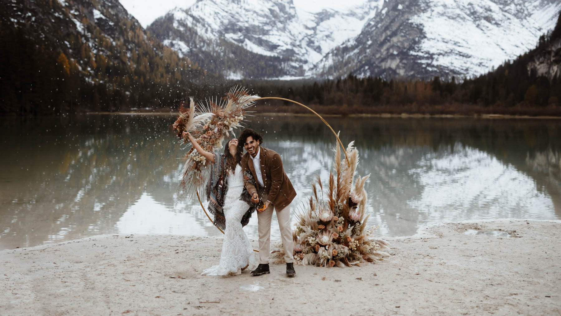 Champagne toss on elopement in the DOlomites Italy with boho floral arch